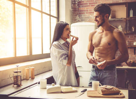 personas comunicandose: Beautiful young couple is looking at each other and smiling while eating toast in kitchen at home Foto de archivo