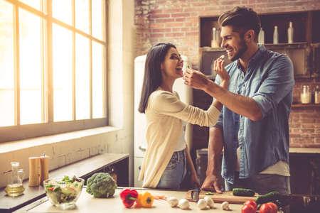 美しい若いカップルはお互いを餌と自宅のキッチンで料理をしながら笑みを浮かべて 写真素材