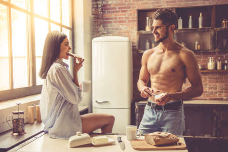 muscular woman: Beautiful young couple is looking at each other and smiling while eating toast in kitchen at home Stock Photo