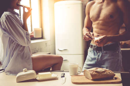 Cropped image of beautiful young passionate couple eating toasts and drinking coffee in kitchen at home