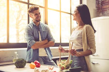 美しい若いカップルが話している、カメラ目線と自宅のキッチンで料理をしながら笑みを浮かべてします。女性はサラダを混合します。