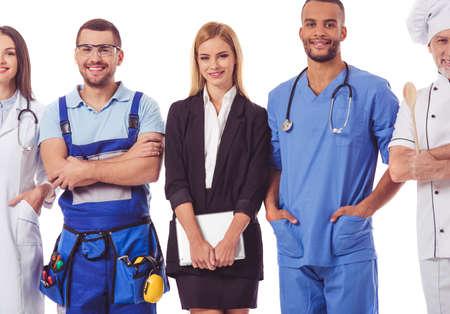 diferentes profesiones: gente bonita de diferentes profesiones en los uniformes están mirando a la cámara y sonriendo, aislado en blanco