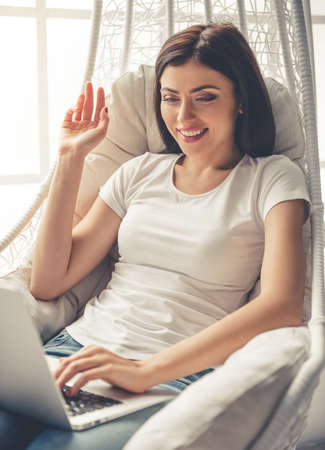 Beautiful girl in casual clothes is using a laptop, waving and smiling while sitting in armchair near the window at home Stock Photo