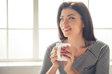 Portrait of beautiful young businesswoman in casual clothes holding a cup, looking away and smiling while working at home