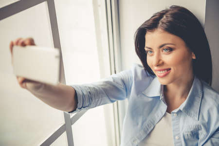 Beautiful girl in casual clothes is doing selfie using a smartphone and smiling while sitting near the window at home
