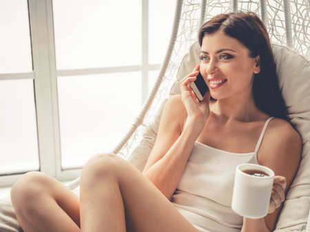 Beautiful girl in pajama is talking on the mobile phone, holding a cup of tea and smiling while sitting in armchair near the window at home