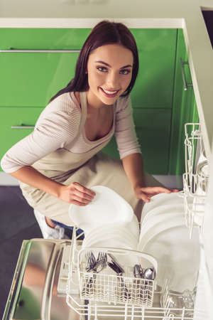 Beautiful young woman in apron dishes into dishwasher, looking at camera and smiling while washing dishes in kitchen