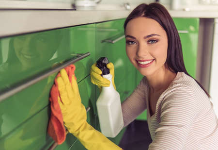 Beautiful young woman is using a detergent and a duster, looking at camera and smiling while cleaning kitchen