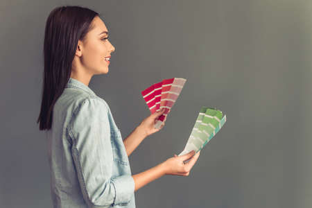 schemes: Side view of beautiful young woman holding color schemes and smiling, on gray background