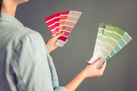 schemes: Cropped image of beautiful young woman holding color schemes, on gray background