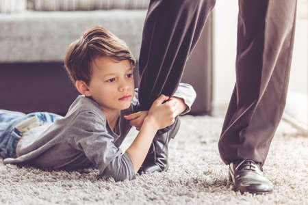 sadly: Little boy is trying not to let his father go, holding his leg and looking sadly