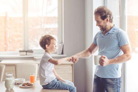 부엌에서 간식을 먹고있는 동안 아버지와 아들이 5 개를주고 웃고 있습니다.