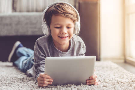 Kleiner Junge in den Kopfhörern benutzt ein digitales Tablett und lächelt, während er zu Hause auf dem Boden liegt