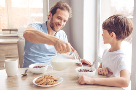 Father and son are smiling while having a breakfast in kitchen. Dad is pouring milk into bowls Zdjęcie Seryjne