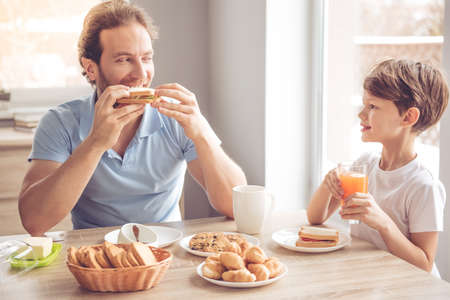 Father and son are talking and smiling while having a breakfast in kitchen