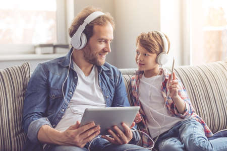 Father and son in headphones are listening to music using gadgets and smiling while spending time together at home Фото со стока