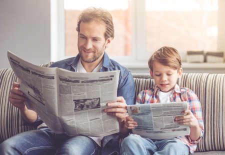 Padre e hijo están leyendo periódicos y sonriendo mientras pasan tiempo juntos en casa. Foto de archivo - 66197467
