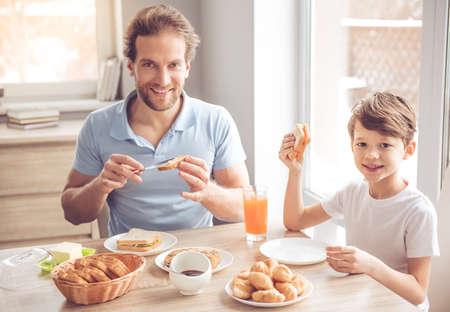 Padre e hijo están mirando a la cámara y sonriendo mientras toma un desayuno en la cocina Foto de archivo - 66197482