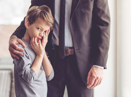 room to let: Little boy is looking at camera and wiping eyes while his father is hugging him Stock Photo