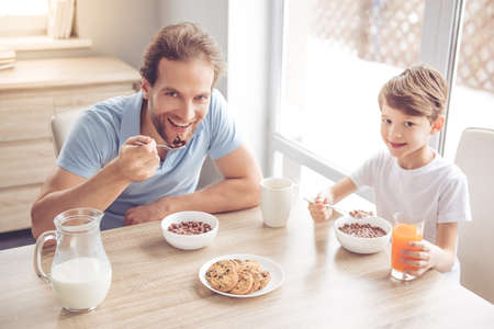 Father and son are looking at camera and smiling while having a breakfast in kitchen Zdjęcie Seryjne