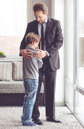 room to let: Handsome young father in classic suit is hugging his son while little boy is crying Stock Photo