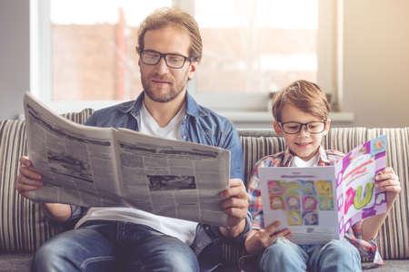 아버지와 아들이 집에서 함께 시간을 보내면서 신문을 읽고 웃고 있습니다. 스톡 콘텐츠