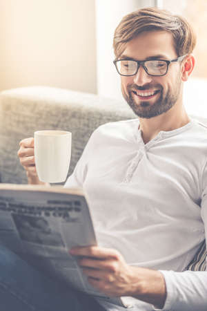 Handsome man in eyeglasses is reading a newspaper, holding a cup and smiling while sitting on couch at home