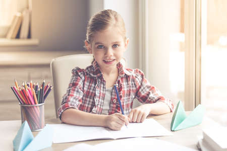 Cute little girl is drawing, looking at camera and smiling while spending time at home Stock Photo