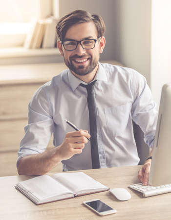 Handsome businessman in eyeglasses is making notes, using a computer and smiling while working in office