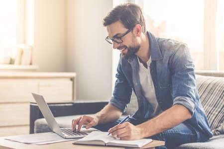 Jóképű üzletember a szemüvegben jegyzeteket és mosolyogva dolgozik egy laptop otthon