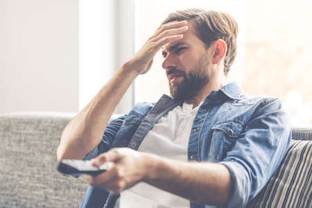 revulsion: Handsome man is feeling disgust while watching TV at home Stock Photo