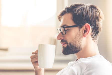 안경에 잘 생긴 남자는 커피의 향기를 냄새 맡고 집에서 쉬고있는 동안 웃고있다. 스톡 콘텐츠