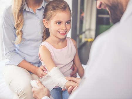 美しい若い母親と小児科医の小さな娘。医者は少し患者の腕に包帯を巻く
