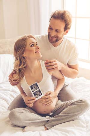 Hermosa mujer embarazada y su marido hermoso son la celebración de una ecografía, abrazando y sonriendo mientras está sentado en la cama Foto de archivo