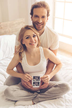sonograma: Hermosa mujer embarazada y su marido hermoso son la celebración de una ecografía, abrazando y sonriendo mientras está sentado en la cama Foto de archivo