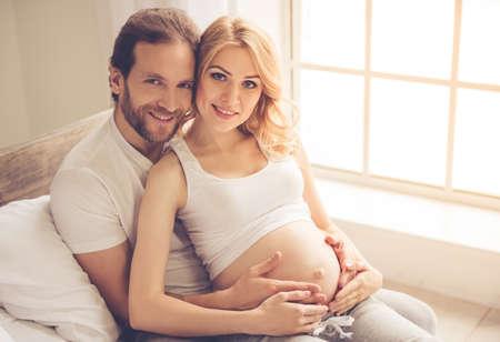 아름 다운 임신 한 여자와 그녀의 잘 생긴 남편 포옹 하 고 웃 고 함께 시간을 보내고