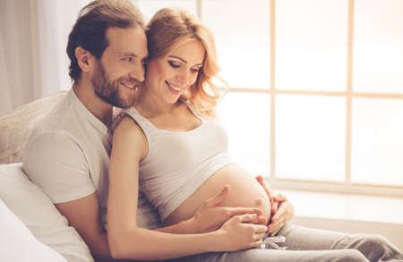 美しい妊娠中の女性と彼女のハンサムな夫を抱き締めると、一緒に時間を過ごしながら笑みを浮かべて