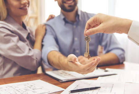 Cropped image of beautiful couple taking keys from the real estate agent and smiling