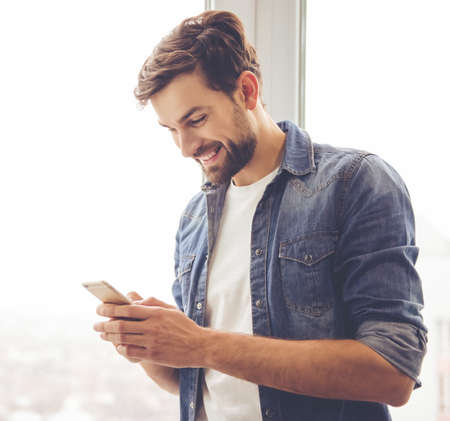 Handsome man in jean clothes is using a smartphone and smiling while standing near the window Banco de Imagens