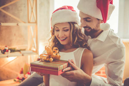 Beautiful young woman and man in Santa hats are celebrating Christmas at home. Guy is giving his girlfriend a gift box