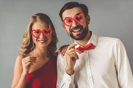 Beautiful elegant girl in red dress and guy in classic shirt and red bow tie are holding a paper heart glasses and smiling, on gray background