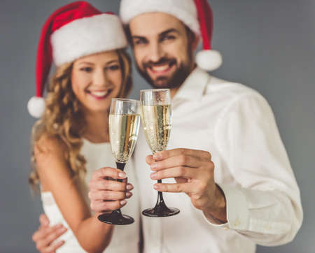 christmas hats: Beautiful young couple in Santa hats is holding glasses of champagne, looking at camera and smiling, on gray background