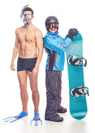 flippers: Summer and winter sports. Full length portrait of young man with diving equipment and woman with snowboard