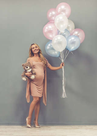 Full length portrait of beautiful pregnant woman holding balloons and teddy bear, looking at camera and smiling, on gray background Stock Photo