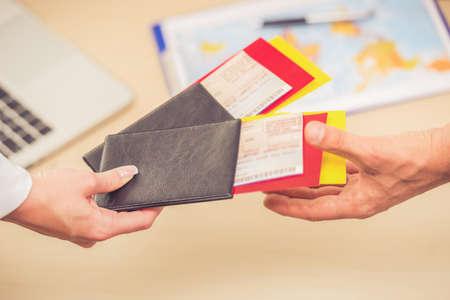 旅行代理店を訪問している間航空券とパスポートを保持している人間の手のクローズ アップ
