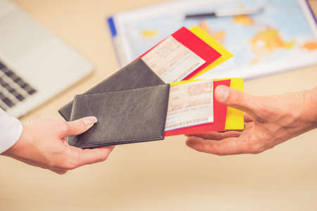 Close-up of human hands holding tickets and passports while visiting travel agency