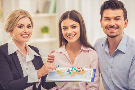 Beautiful female travel agent and happy young couple are choosing tour and smiling while sitting in office