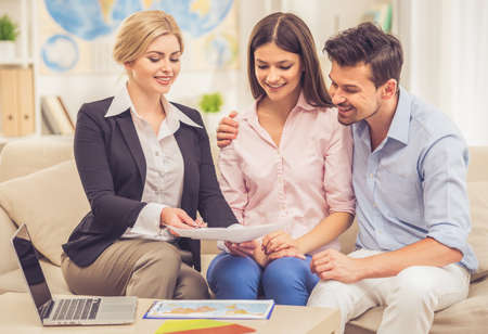 boarding card: Beautiful female travel agent is offering young couple tours and smiling while sitting on couch in office Stock Photo
