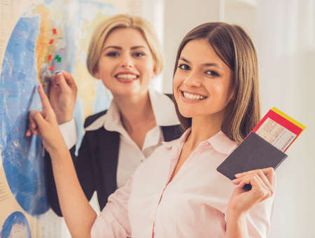 Beautiful female travel agent and her client are standing near map with destination signs on it and smiling