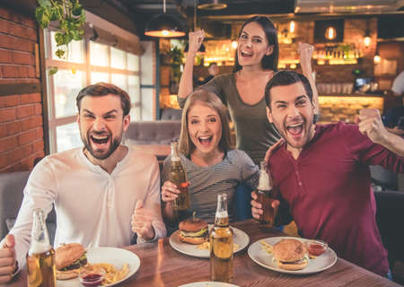 Gelukkige vrienden juichen voor het team en lachend terwijl hij samen tijd doorbrengen in cafe